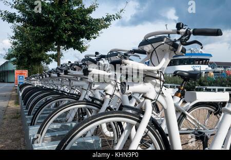 Bikes lined up on sidewalk in Copenhagen Denmark - Stock Photo