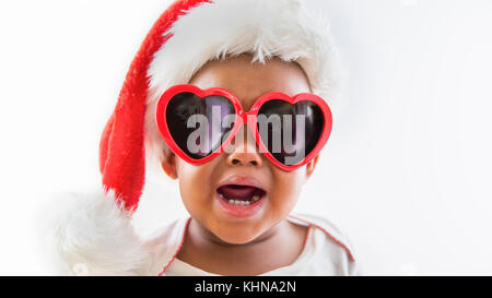 Funny closeup portrait of upset Black African American baby wearing heart sunglasses and Santa hat on white background - Stock Photo