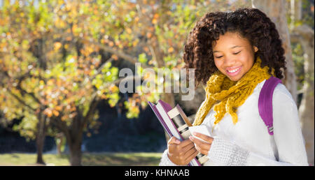 Pretty African American Black female student texting or using mobile phone. Room for copy or text over Fall trees - Stock Photo