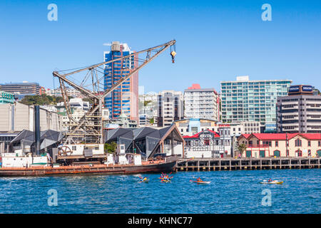 Wellington Waterfront, with the floating crane Hikitia, Te Raukura and the Boatshed, and people kayaking in the - Stock Photo