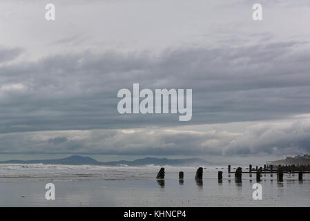 View looking out to sea across to the Lynn peninsula from Barmouth beach with groynes on the sandy beach in the - Stock Photo