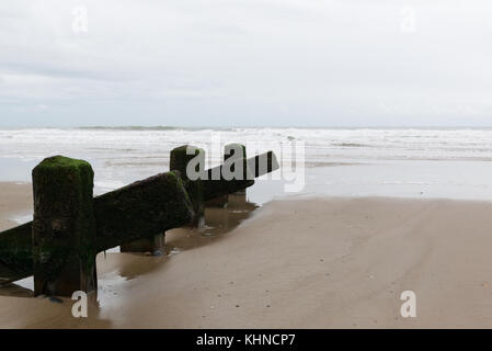 View looking out to sea from Barmouth beach with groynes providing leading lines on the sandy beach in the foreground. - Stock Photo