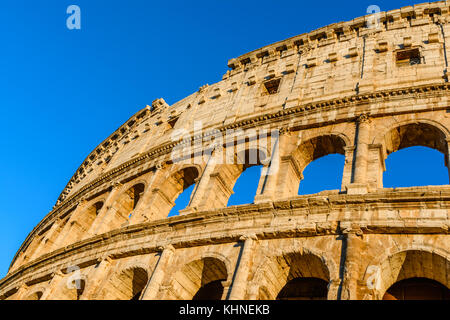 Sunset colors on Colosseum, an elliptical amphitheatre in the centre of Rome,Italy.Built of concrete and stone,it - Stock Photo
