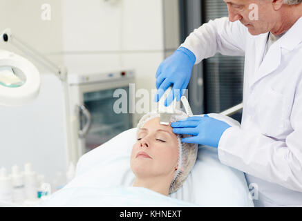 Modern cosmetician doing anti-wrinkle procedure on his client face - Stock Photo