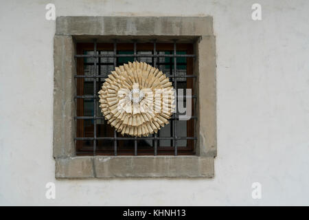 a paper wheel decorates a window of a house in the historic center of Venzone, Friuli, Italy - Stock Photo
