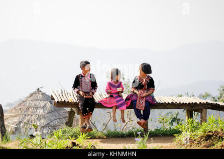 Lovely boy and girl playing outdoors while posing wearing ethnic clothes from the Hmong tribe, indigenous people of Thailand.