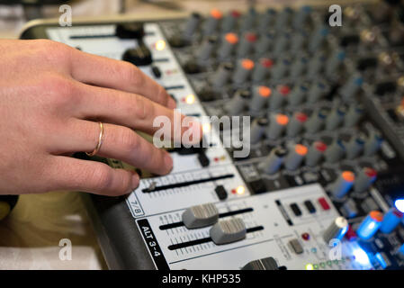DJ working on a audiomixer at a nightclub - Stock Photo