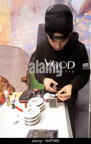 Young boy repairing vape tank on a table. Vape&Trade Expo at the Akko International expo-center. March 19, 2017. - Stock Photo