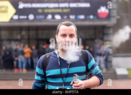 Young urban man smoking vape in front of blurred crowd of people. Vape&Trade Expo at the Akko International expo - Stock Photo