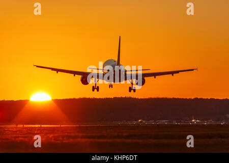 Airplane landing flying airport sun sunset vacation holidays travel traveling plane aircraft travelling - Stock Photo
