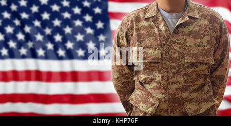 Soldier in a USA military digital pattern uniform, standing on an American flag background - Stock Photo