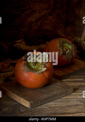 Top view  kaki fruits on wooden table and chestnuts - Stock Photo