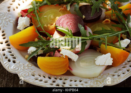Healthy Beet Salad with red, white, golden beets, arugula, nuts, feta cheese on wooden background - Stock Photo