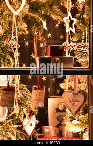 A shop window decorated for Christmas or the festive season of xmas with tinsel and baubles and stars in a creative - Stock Photo