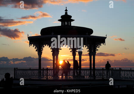 The setting sun silhouettes the Bandstand on Brighton seafront. - Stock Photo
