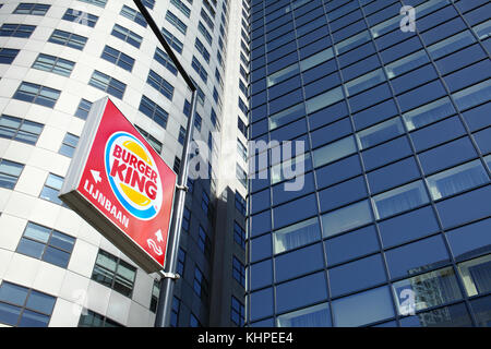 A fast food sign among high rise office blocks on Weena, Rotterdam city centre, The Netherlands. - Stock Photo