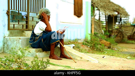 INDIA - JUNE 29 2016: Indian elder lady sitting on the ground, House exterior old woman sitting on steps. - Stock Photo
