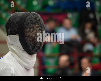 fencer wearing a mask during a sporting event - Stock Photo