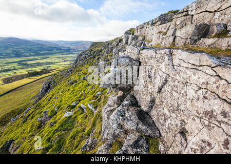 Rocky cliff with weathered limestone on Stags Fell in the Yorkshire Dales, England. Valley of Wensleydale can be - Stock Photo