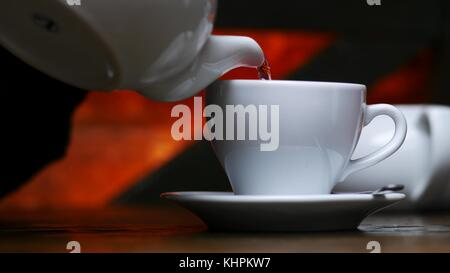 Woman pouring tea from white kettle to cup in cafe - Stock Photo