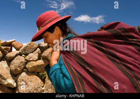 A woman heads home after a hard day in the countryside on the island of Amantani. Amantani Island, Lake Titicaca, - Stock Photo