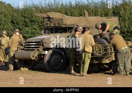 World War Two re-enactors in US Army uniforms, with M3 Half-track and Willys Jeep, Cosby Victory Show, UK. - Stock Photo