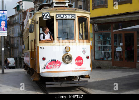 Tram stopping on the Rua da Assunção in the historical old town of Porto, Portugal. - Stock Photo