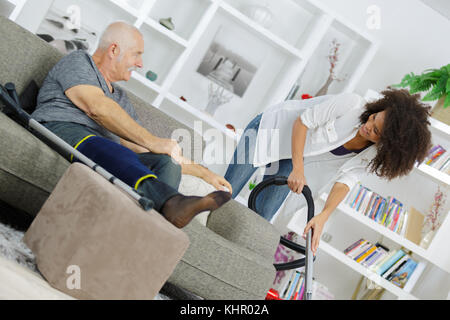 senior man walking using crutches on sofa talking to assistant - Stock Photo