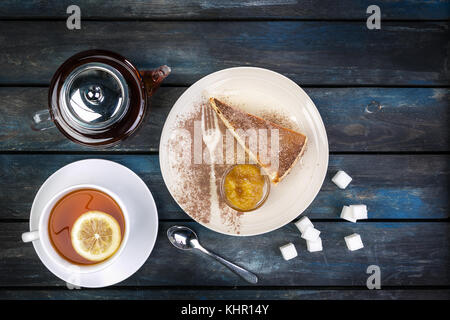 Slice of Cheesecake with jam and tea kettle with lemon on a colored wooden background. Top view. - Stock Photo