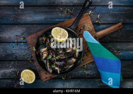 Delicious mussels. Serving on a hot frying pan with herbs spices and lemon on a colored wooden background. Top view. - Stock Photo