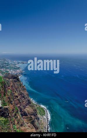 View of Atlantic ocean, blue sky, rocky coastline and part of Camara de Lobos town as seen from highest european - Stock Photo