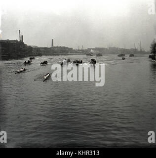 1950s, historial picture showing the boats and flotilla of the famous university rowing race, the Oxford & Cambridge - Stock Photo