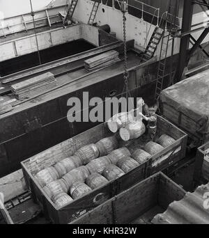 1950s, historical, two male dockers supervising the loading from a rail wagon, of a cargo of wooden barrels of sulphate - Stock Photo