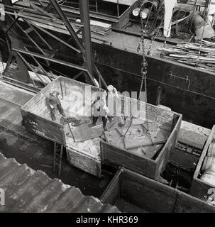 1950s, historical picture from overhead showing male workers in an LMS wagon putting sheets of heavy metal cargo - Stock Photo