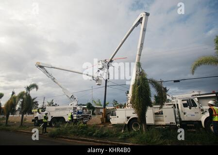 Utility workers repair a damaged electrical transformer to restore power during relief efforts in the aftermath - Stock Photo