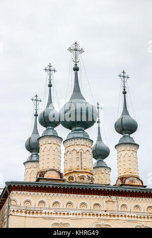 Small ornamented towers of the Log-Jerusalem church with metal onion shaped domes under a cloudy sky, Suzdal, Golden - Stock Photo