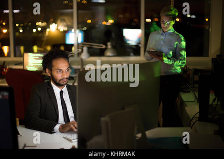 Busy dim open plan office: mixed race manager wearing stylish suit working on promising project with help of computer while his pretty young colleague