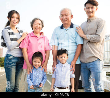three generations family standing together outdoors - Stock Photo