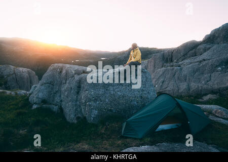 Alone tourist near his tent - Stock Photo