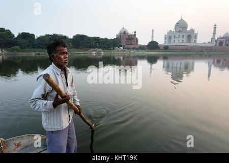 Fisherman on his traditional old boat paddling on Yamuna river, Taj Mahal reflection at the back, Agra, Uttar Pradesh, - Stock Photo