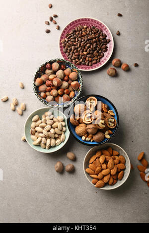 Various nuts in bowls, food above - Stock Photo