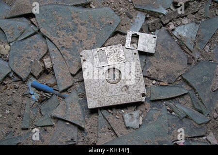 Destroyed and abandoned vintage floppy disc. Forgotten technologies - 3.5 inch disk in plastic case on broken glass. - Stock Photo