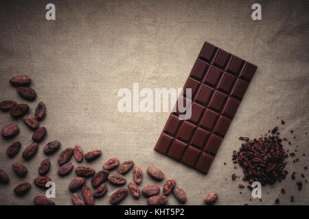 Dark chocolate and Raw cocoa beans. Background texture of old jute - Stock Photo