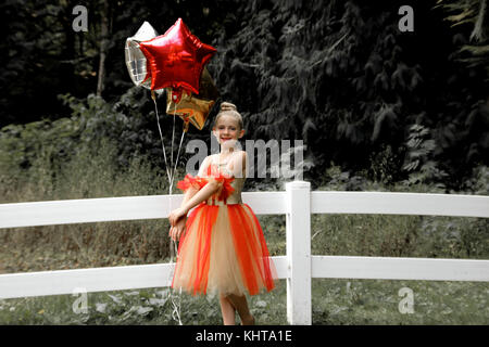 Outdoor photo of child ballerina posing in front of trees and a fence, holding star-shaped balloons, wearing a tutu. - Stock Photo