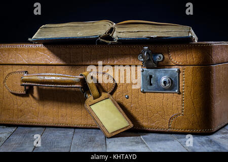 Old stylish suitcase. Old books in a suitcase. Suitcase on a wooden table. Black background - Stock Photo