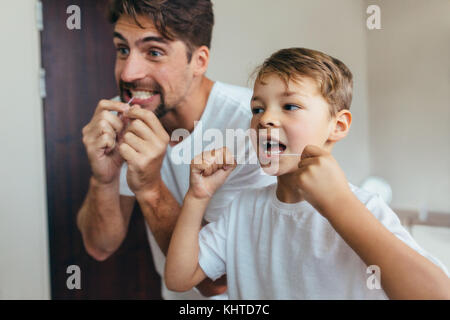 Little boy with his father in bathroom cleaning teeth with dental floss. Both looking in mirror and brushing teeth. - Stock Photo