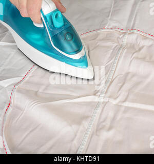 Objects Hands action - Closeup hand worker ironing by the electric iron white fabric. - Stock Photo