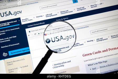 MONTREAL, CANADA - NOVEMBER 7, 2017: usa.gov website with green card regulations page under magnifying glass. The - Stock Photo