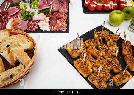 cheese sticks. Food tray with delicious salami, pieces of sliced ham, sausage, salad. Bread. Tomatoes stuffed with - Stock Photo