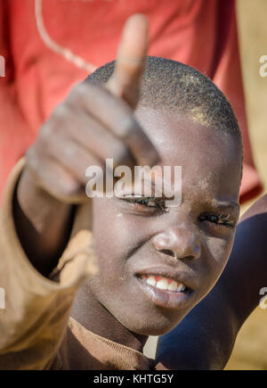CAOTINHA, BENGUELA, ANGOLA - MAY 11 2014: Portrait of unidentified African boy with dirty face showing a thumbs - Stock Photo